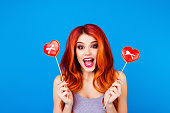 istock Portrait of stylish funny happy carefree girl with ginger hair holding sweet gingerbread with red heart form with stick while standing on blue background 941408096