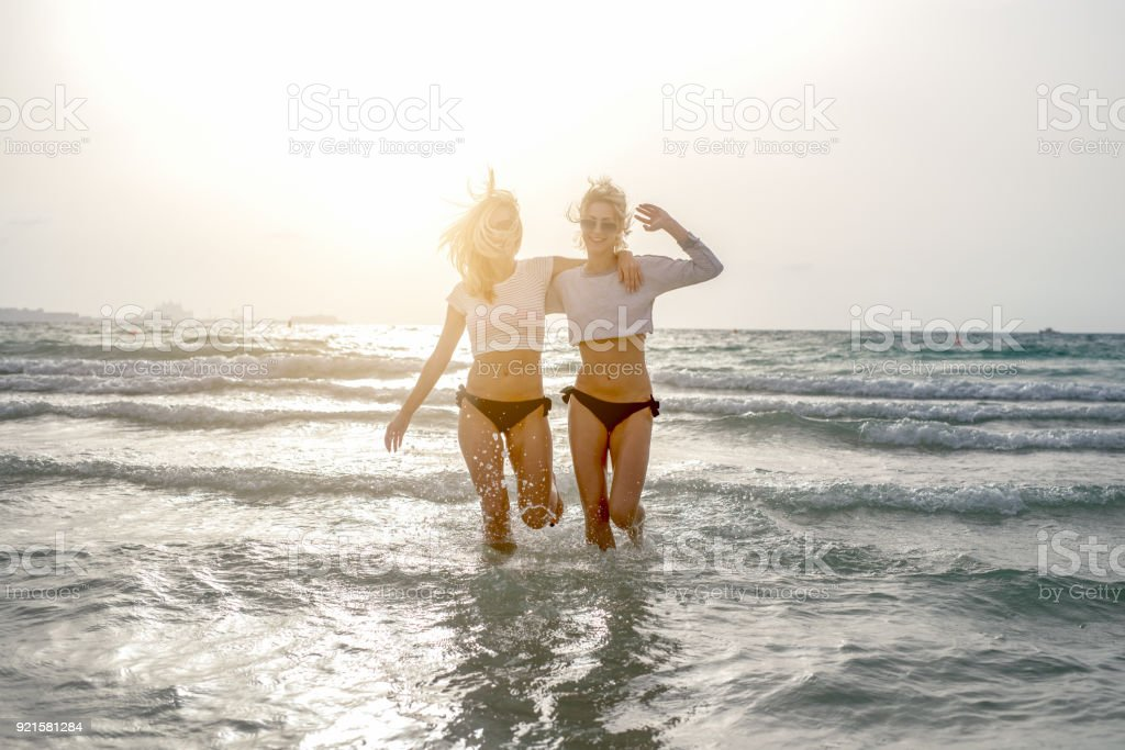 Portrait of stylish girlfriends standing in crystal ocean at sunset stock photo