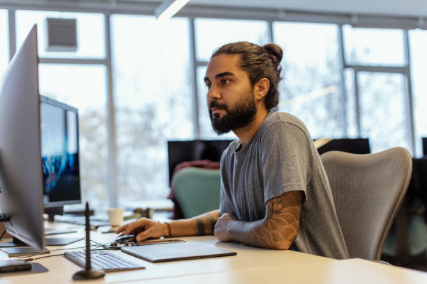 portrait of stylish hipster guy with  tattoo on hand, writes notes in computer at office - designer professionista foto e immagini stock