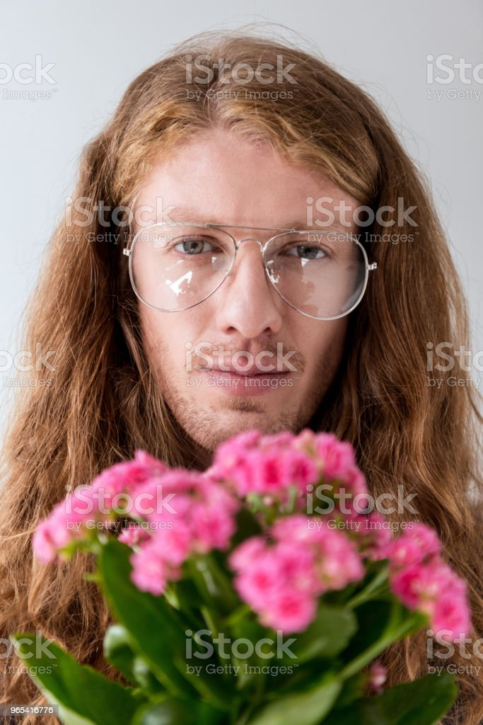 portrait of stylish man with curly hair with bouquet of pink flowers looking at camera - Zbiór zdjęć royalty-free (Bukiet)