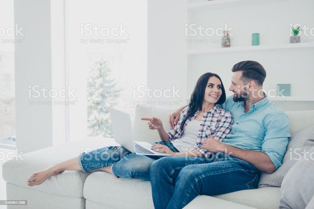 d8e2229e42 Retrato de casal moderno elegante escolher mercadorias na internet loja  gesticulando com o dedo indicador desfrutando