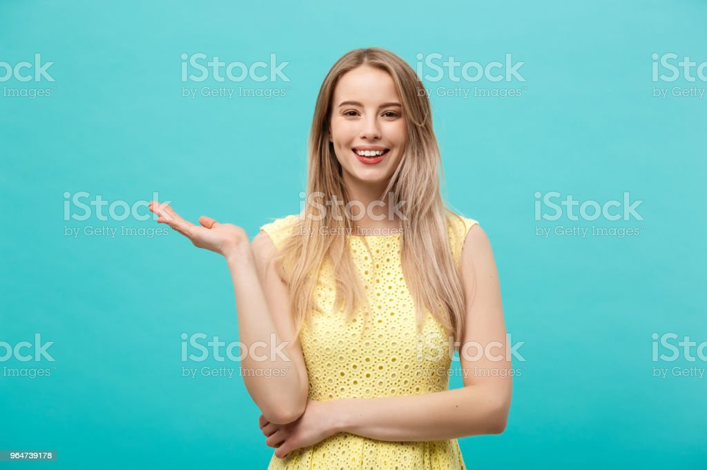 Portrait of stylish, nice, cute, caucasian woman with hairstyle in yellow dress holding in hand on empty places, copy spaces on her palms, looking at camera, isolated on blue background royalty-free stock photo