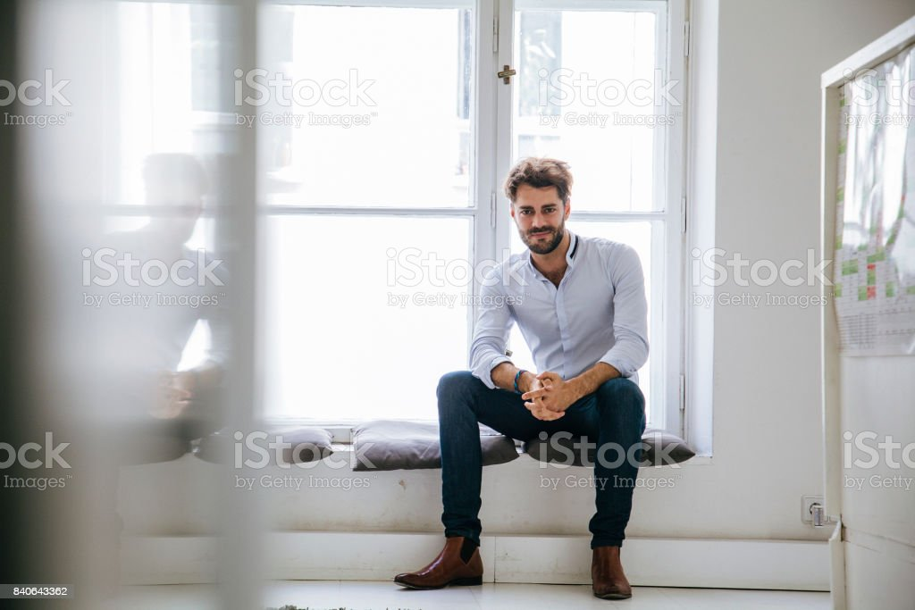 Portrait Of Stylish Office Manager Sitting By Window stock photo