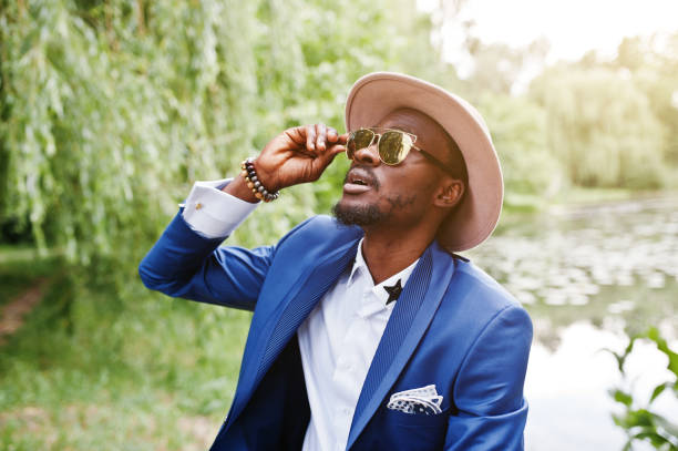 Portrait of stylish rich black man at blue jacket, hat and sunglasses stock photo