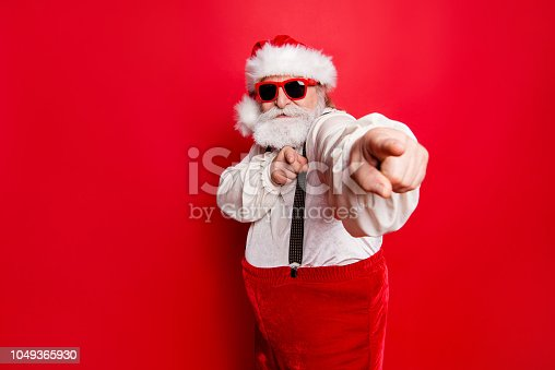 istock Portrait of stylish trendy happy joyful funky funny confident Santa pointing at camera prepared ready to feast festive party promo sale discount isolated over red background 1049365930