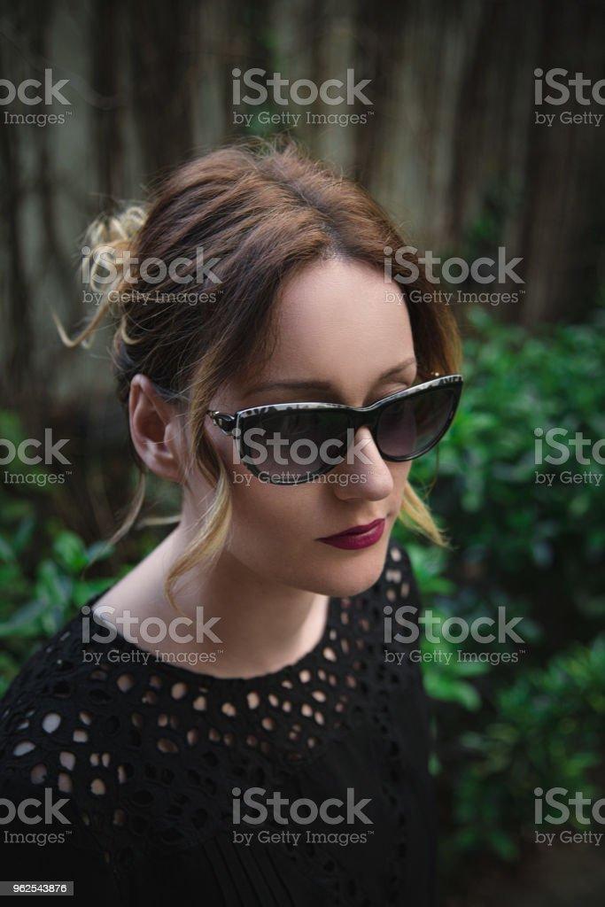Retrato de uma mulher elegante em óculos escuros e camisa preta elegante - Foto de stock de Adulto royalty-free