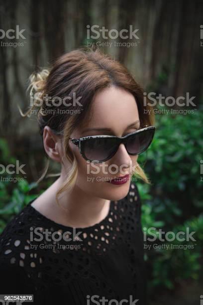 Foto de Retrato De Uma Mulher Elegante Em Óculos Escuros E Camisa Preta Elegante e mais fotos de stock de Adulto