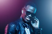 istock Portrait of stylish young african man listening music with wireless earphones 1153003845