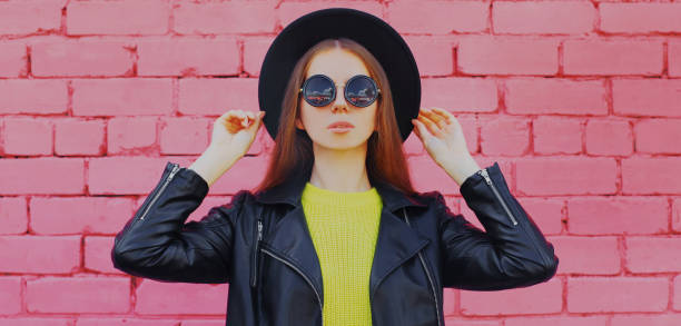 Portrait of stylish young woman wearing a black rock style on a pink brick wall background stock photo