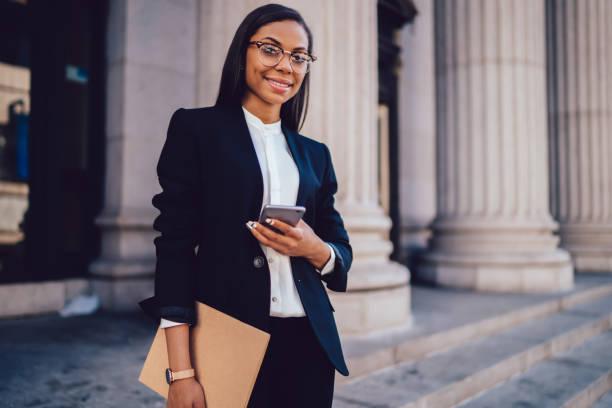 portret van succesvolle afro-amerikaanse zakenvrouw gekleed in stijlvolle pak holding in de hand map en mobiele telefoon, terwijl staande buitenshuis in de buurt van financial office, jonge vrouw advocaat met behulp van smartphone - juridisch beroep professioneel beroep stockfoto's en -beelden