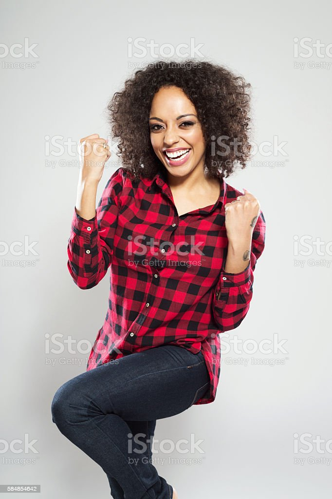 Portrait of successful afro american young woman Portrait of successful afro american young woman wearing casual red checkered shirt, standing against grey background, raising fists and laughing at camera. Adult Stock Photo