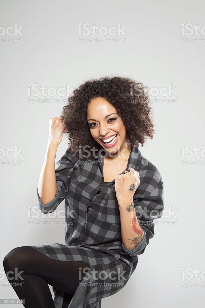 Portrait of successful afro american young woman Portrait of successful afro american young woman wearing casual checkered dress, standing against grey background, laughing at camera. Adult Stock Photo