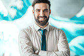 Portrait of successful bearded Caucasian businessman with shirt and tie standing with arms crossed in office. on wrist wristwatch. Starve your distractions, feed your focus.