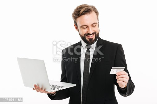 Portrait of successful businessman smiling and holding laptop and plastic credit card in hands isolated over white background