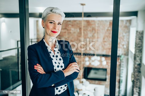 Portrait of beautiful confident smiling businesswoman in modern office. Businesswoman standing with arms crossed in front of glass wall and looking at camera.