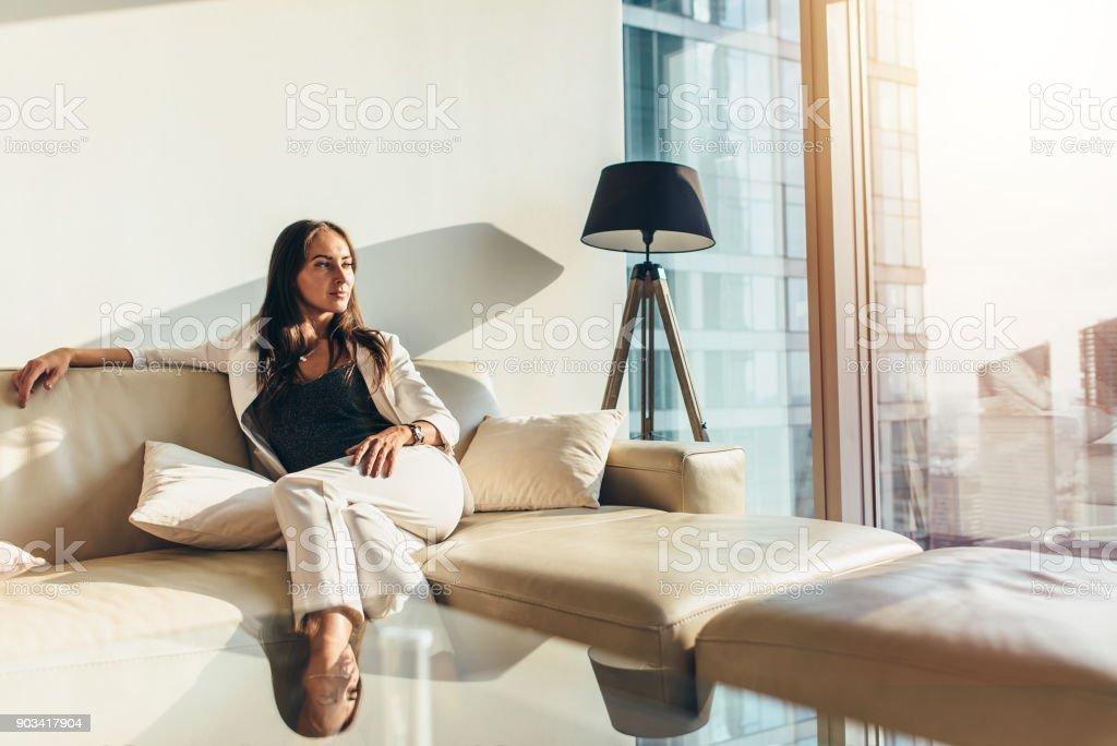 Portrait d'affaires prospère port élégant costume formel assis sur le canapé en cuir relaxant après le travail à la maison photo libre de droits