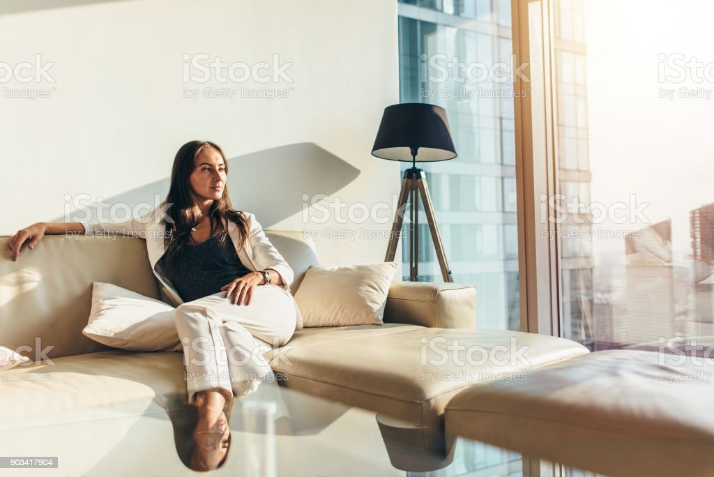 Portrait of successful businesswoman wearing elegant formal suit sitting on leather sofa relaxing after work at home stock photo