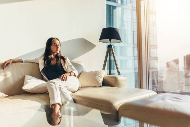 portrait of successful businesswoman wearing elegant formal suit sitting on leather sofa relaxing after work at home - enjoying wealthy life imagens e fotografias de stock