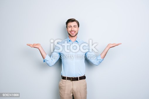 istock Portrait of successful, cheerful, cute, young man presenting start up, new product showing copy space on his palms in two sides, looking at camera, standing over grey background 926241666