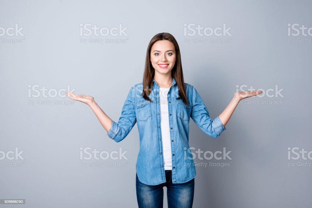 Portrait of successful cheerful cute young woman presenting something, showing copy space on her palm in two sides, looking at camera, standing over grey background royalty-free stock photo