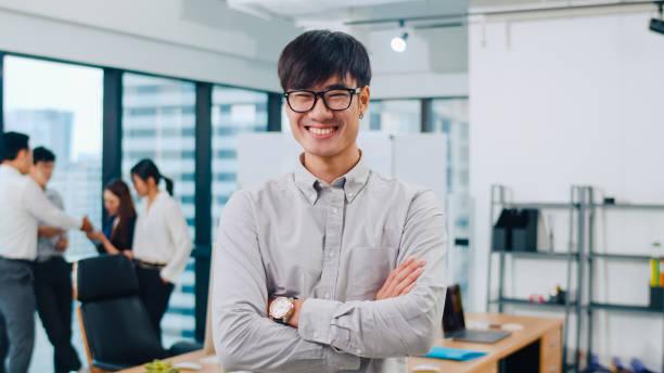 Porträt von erfolgreichen stattlichen Geschäftsmann smart Casual Wear Blick auf die Kamera und lächelnd, Arme gekreuzt in modernen Büroarbeitsplatz. – Foto