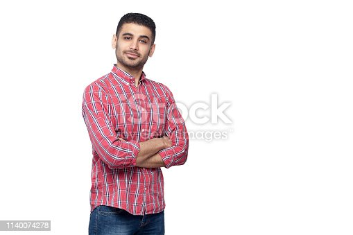 Portrait of successful proud satisfied handsome bearded young man in red checkered shirt standing and looking at camera with crossed arms and smile. indoor studio shot, isolated on white background.