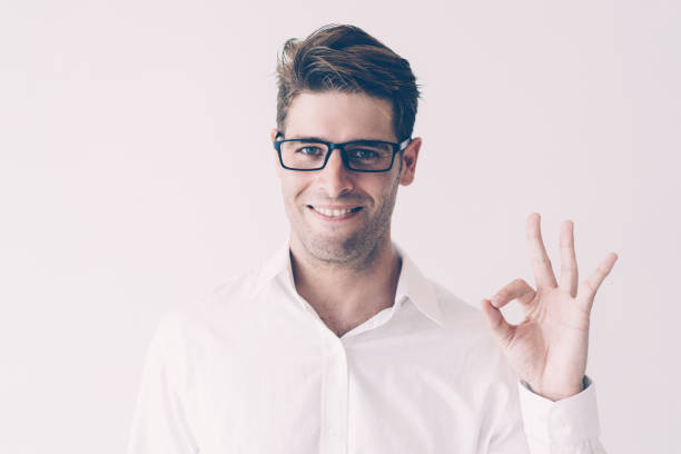 Portrait of successful young businessman showing ok sign stock photo