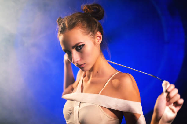 Portrait of sultry beautiful young gymnast woman posing with gymnastics tape stock photo