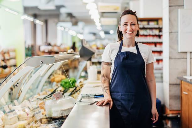 Porträt von Supermarkt-Angestellter steht am Tresen – Foto
