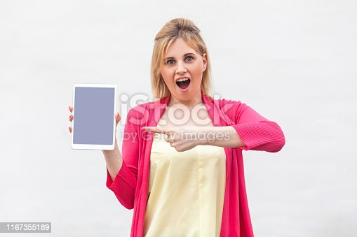 538883870istockphoto Portrait of suprised beautiful young woman in pink blouse standing and holding tablet empty screen and pointing finger to device with opened mouth and looking at camera. 1167355189