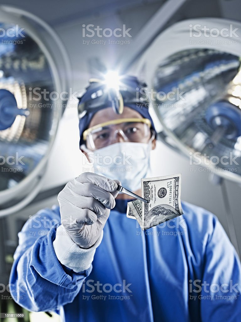 Portrait of surgeon holding one hundred dollar bill under surgical lights stock photo
