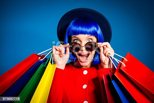 istock Portrait of surprised admired woman looking out glasses with wide open eyes mouth screaming holding colorful packets in hands enjoying seasonal sale having pleasure. Delight inspiration concept 975682218