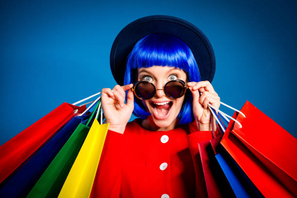 portrait of surprised admired woman looking out glasses with wide open eyes mouth screaming holding colorful packets in hands enjoying seasonal sale having pleasure. delight inspiration concept - smile woman open mouth foto e immagini stock