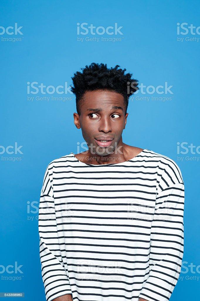 Portrait of surprised afro american guy Portrait of surprised afro american young man wearing striped top, looking away. Studio portrait, blue background. Adult Stock Photo