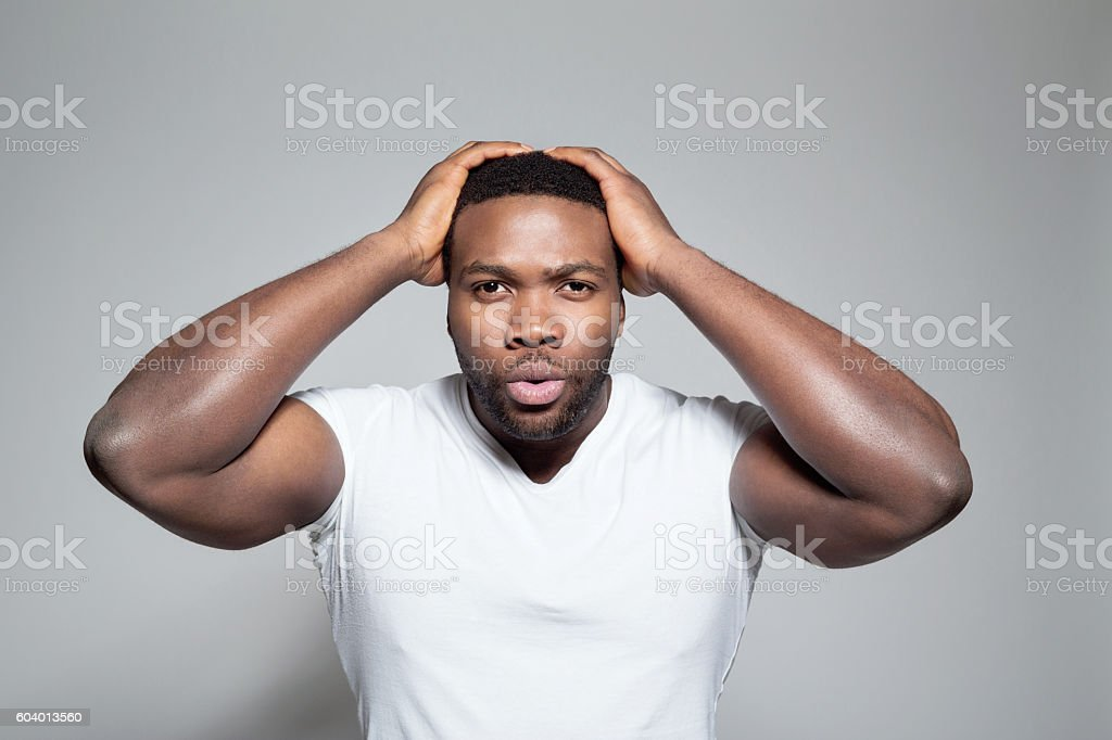 Portrait of surprised afro american young man Portrait of afro american young man wearing white t-shirt, standing against grey background with raised arms, staring at camera. Adult Stock Photo