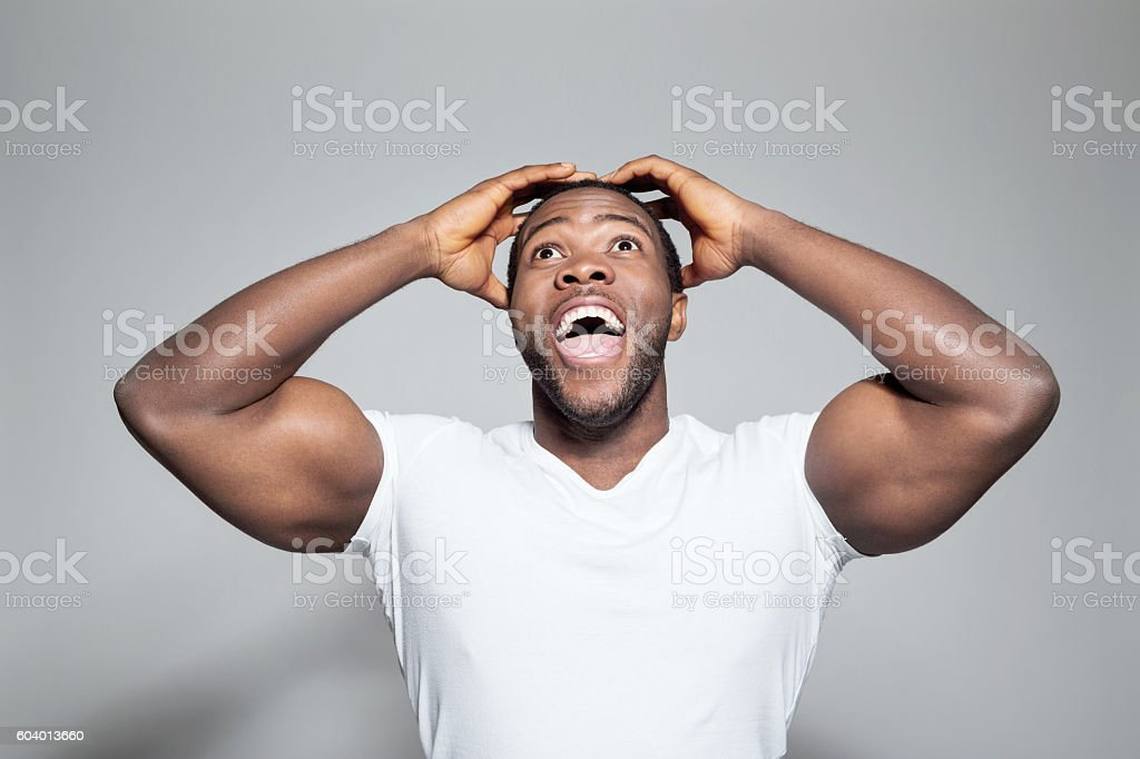 Portrait of surprised afro american young man Portrait of excited afro american young man wearing white t-shirt, standing against grey background with raised arms, looking up and laughing. Adult Stock Photo