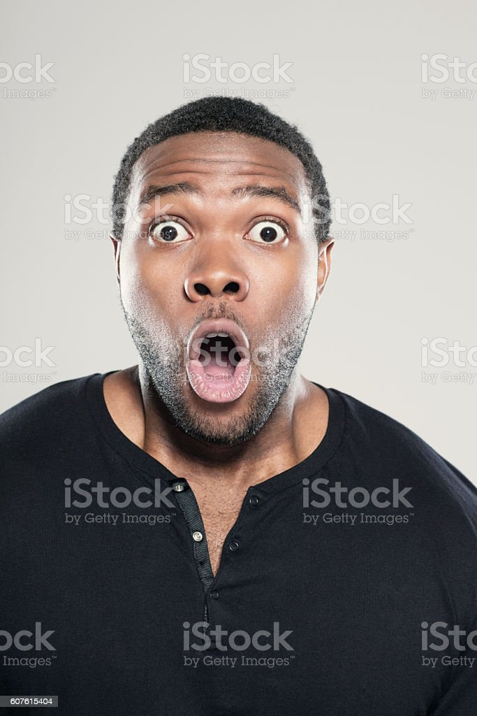 Portrait of surprised afro american young man Portrait of surprised afro american young man wearing black t-shirt, standing against grey background with mouth open, rolling eyes. Adult Stock Photo