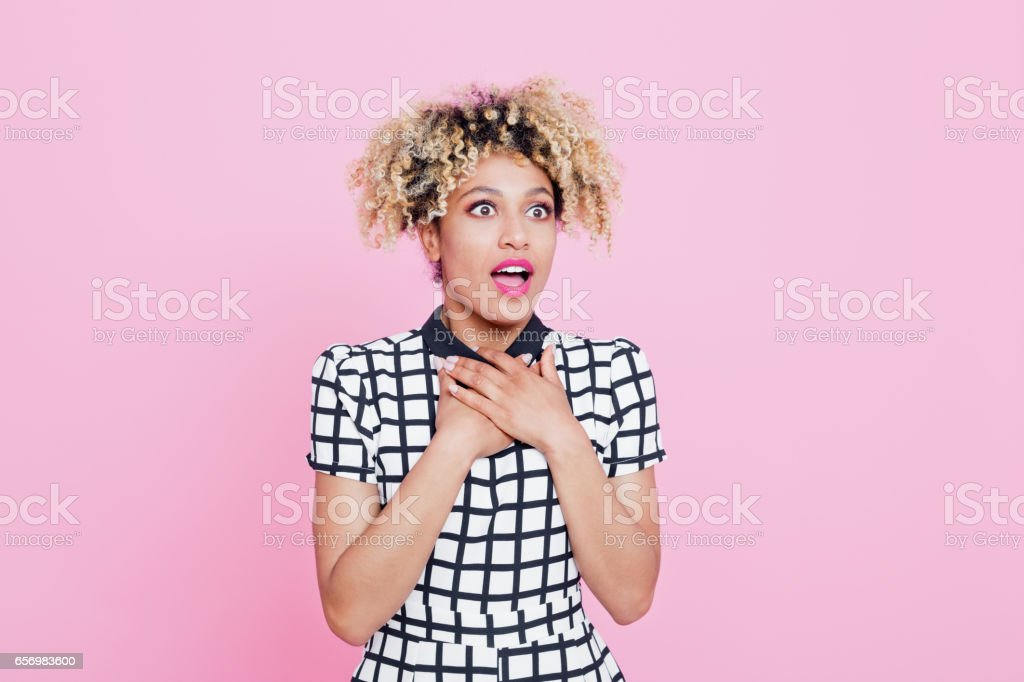 Portrait of surprised afro american young woman Studio portrait of surprised afro american young woman. Pink background. 20-24 Years Stock Photo