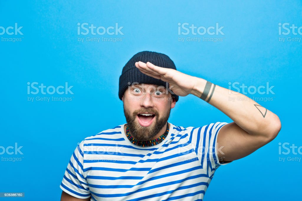 Portrait of surprised bearded sailor against ble background Portrait of happy, surprised bearded man wearing striped t-shirt and beanie hat staring at camera. Studio shot, blue background. 30-34 Years Stock Photo