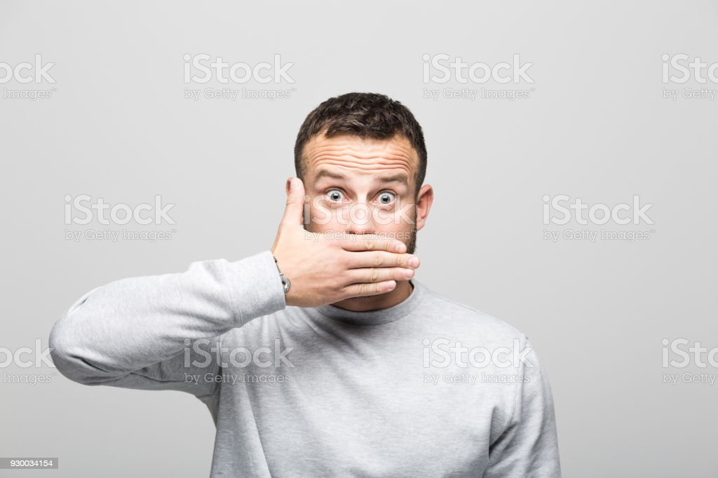 Portrait of surprised bearded young man looking at camera with hand covering mouth Portrait of happy bearded young man staring at camera with hand covering mouth. Studio shot, grey background. 30-34 Years Stock Photo