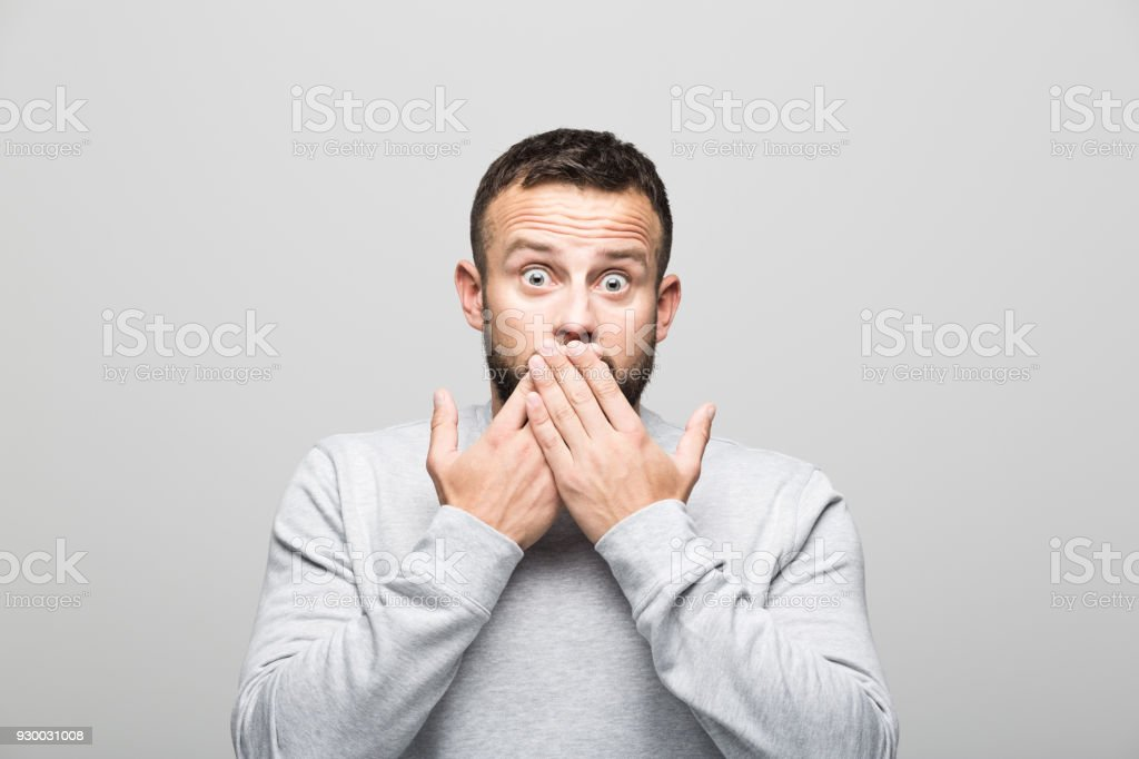 Portrait of surprised bearded young man looking at camera with hands covering mouth Portrait of shocked bearded young man staring at camera with hands covering mouth. Studio shot, grey background. 30-34 Years Stock Photo