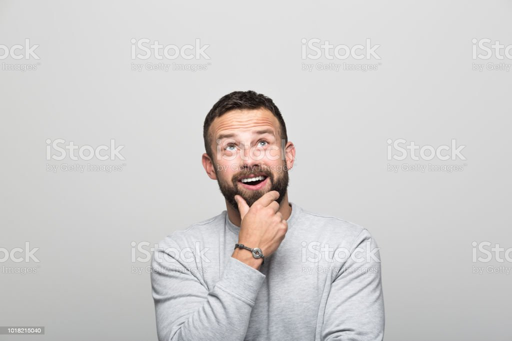 Portrait of surprised bearded young man looking up, grey background Portrait of happy bearded young man looking up with hand on chin. Studio shot, grey background. 30-34 Years Stock Photo