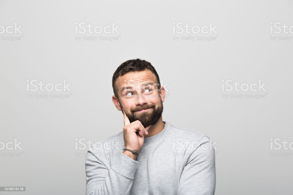 Portrait of surprised bearded young man looking up, grey background Surprised bearded young man looking up with hand on chin. Studio shot, grey background. 30-34 Years Stock Photo