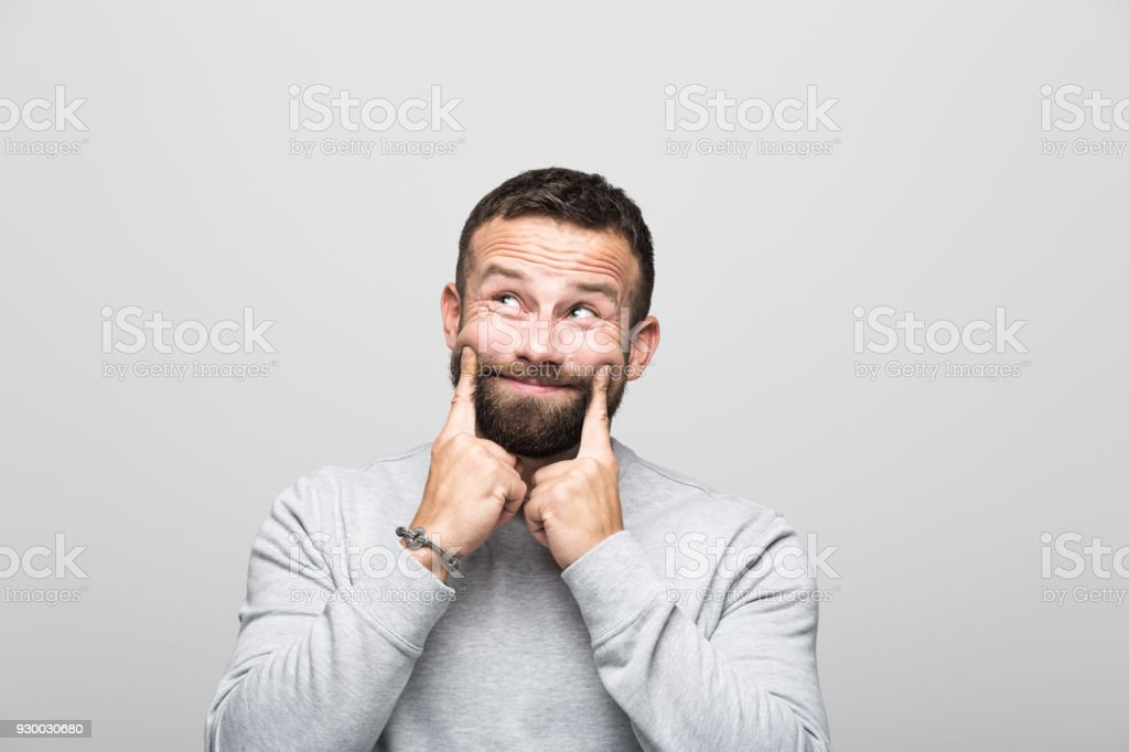 Portrait of surprised bearded young man looking up, grey background Portrait of happy bearded young man looking up with fingers on cheeks. Studio shot, grey background. 30-34 Years Stock Photo