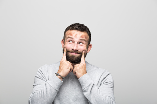 Portrait Of Surprised Bearded Young Man Looking Up Grey Background Stock Photo - Download Image Now