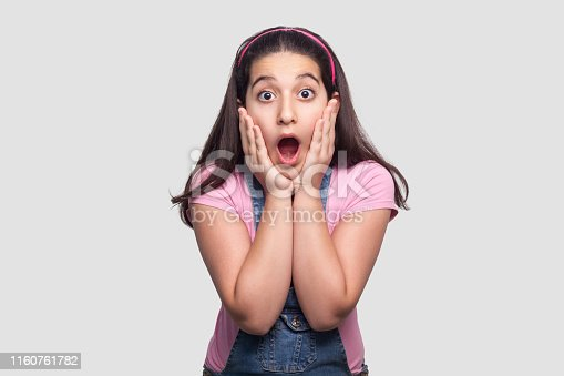 Portrait of surprised beautiful brunette young girl in casual pink t-shirt and blue overalls standing with hands on face and looking with amazed face. studio shot, isolated on light gray background.