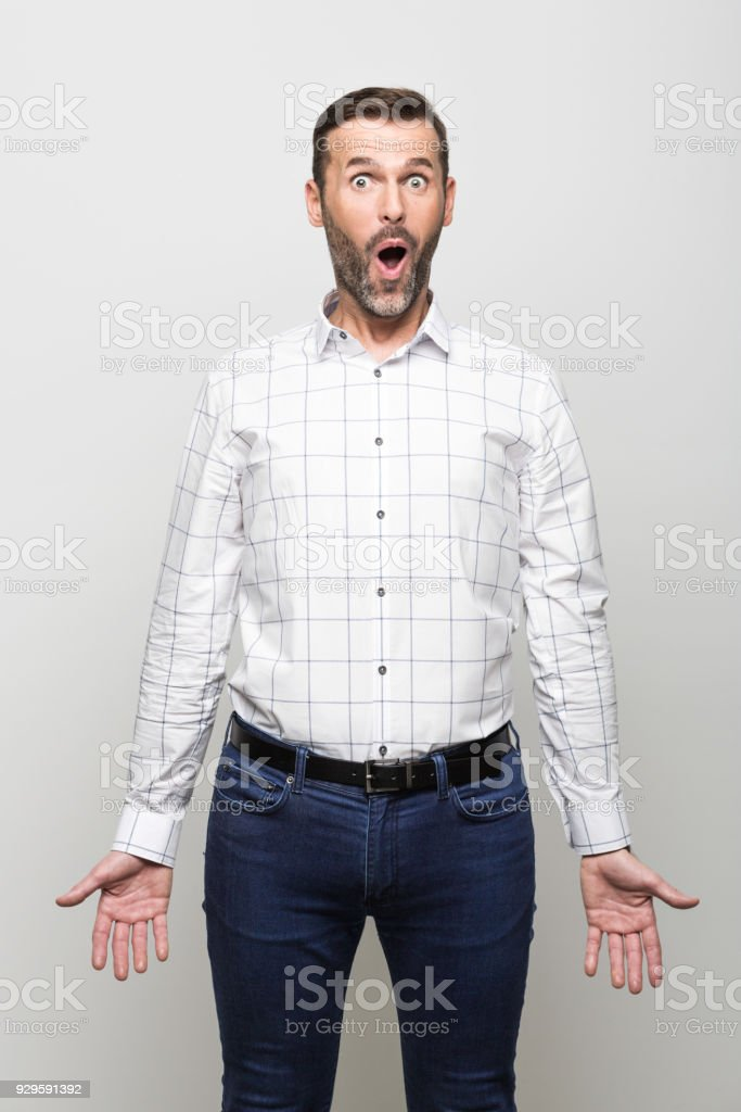 Portrait of surprised businessman staring at camera, grey background Portrait of happy and surprised businessman wearing white shirt and jeans, staring at camera with mouth open. Studio shot, grey background. 30-39 Years Stock Photo