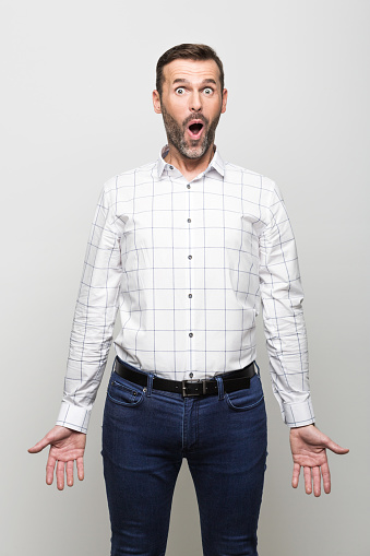 Portrait Of Surprised Businessman Staring At Camera Grey Background Stock Photo - Download Image Now