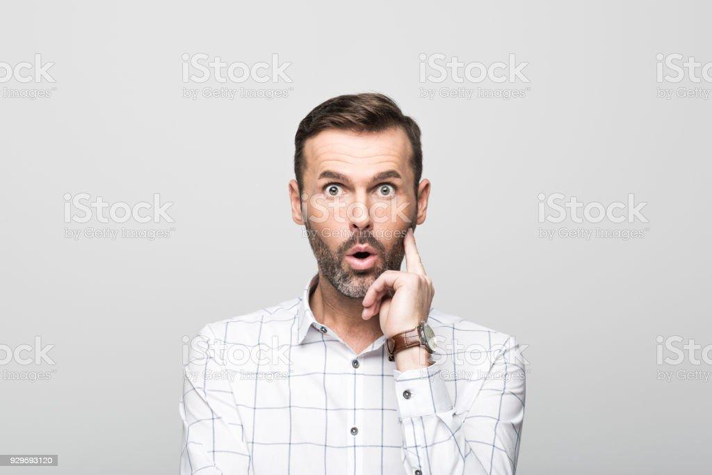 Portrait of surprised businessman staring at camera, grey background Portrait of surprised, handsome businessman wearing white shirt, staring at camera. Studio shot, grey background. 30-39 Years Stock Photo