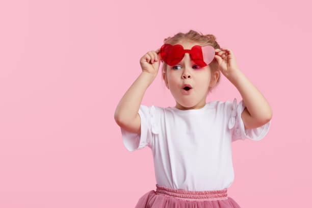 portret van verrast schattige kleine peuter meisje in de hart vorm zonnebril. kind met open mond met plezier geïsoleerd over roze achtergrond. kijkend naar de camera. wow grappig gezicht - alleen één meisje stockfoto's en -beelden
